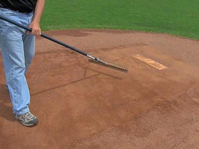 To fortify common wear areas around the mound and home plate with clay you'll need to start with pushing back material.