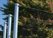 Tensioned overhead cable supports cage — no side poles or overhead structure to cause ball ricochet and no structure to snag or tear netting