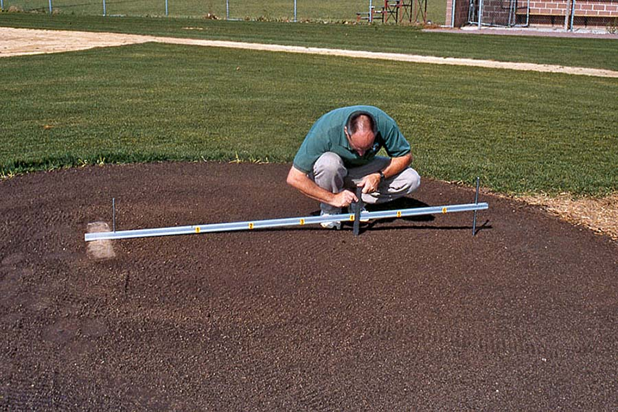 Photo: A groundskeeper measures base distance.